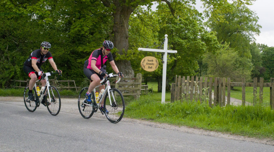 Two cyclists riding past the south ormsby hall sign.
