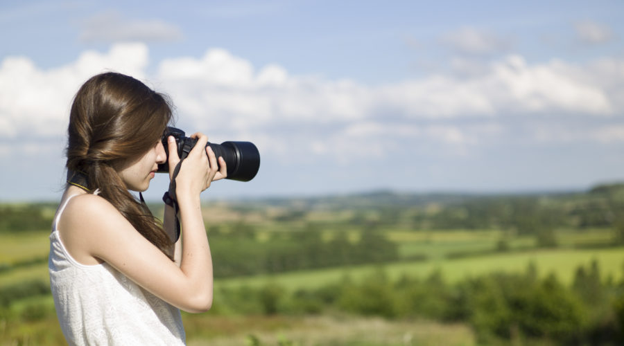 Women in white dress and with long brown hair taking a photo outside with a long-lense camera. Background behind the women features the Lincolnshire Wolds.