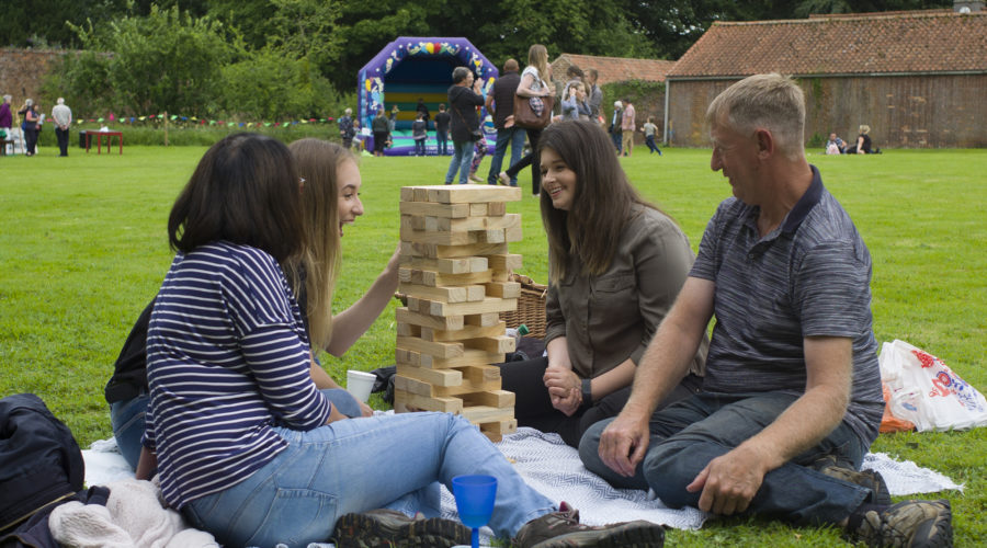 Four people playing giant jenga outside of South Ormsby Hall