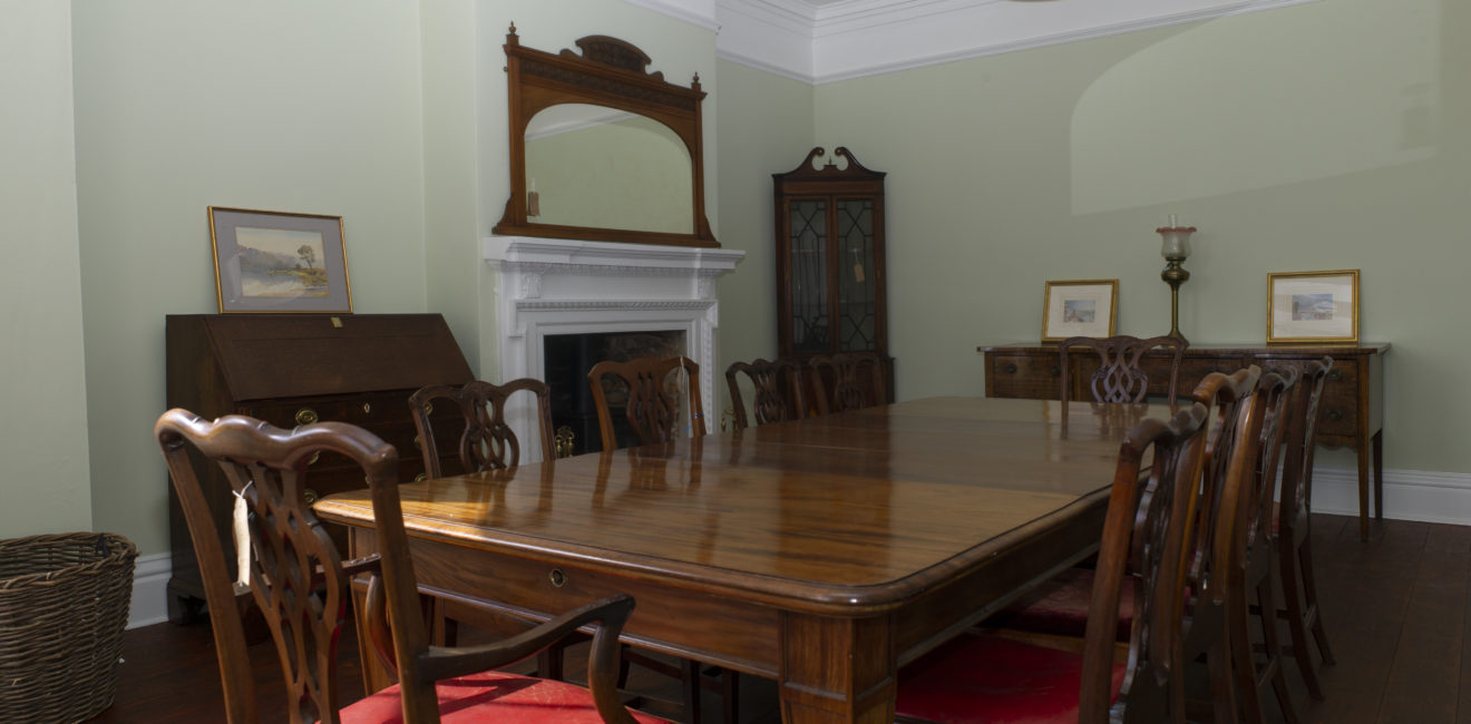 South Ormsby Hall Dining Room. 10 seat table with red cushioned chairs and wooden furniture surrounding the room.