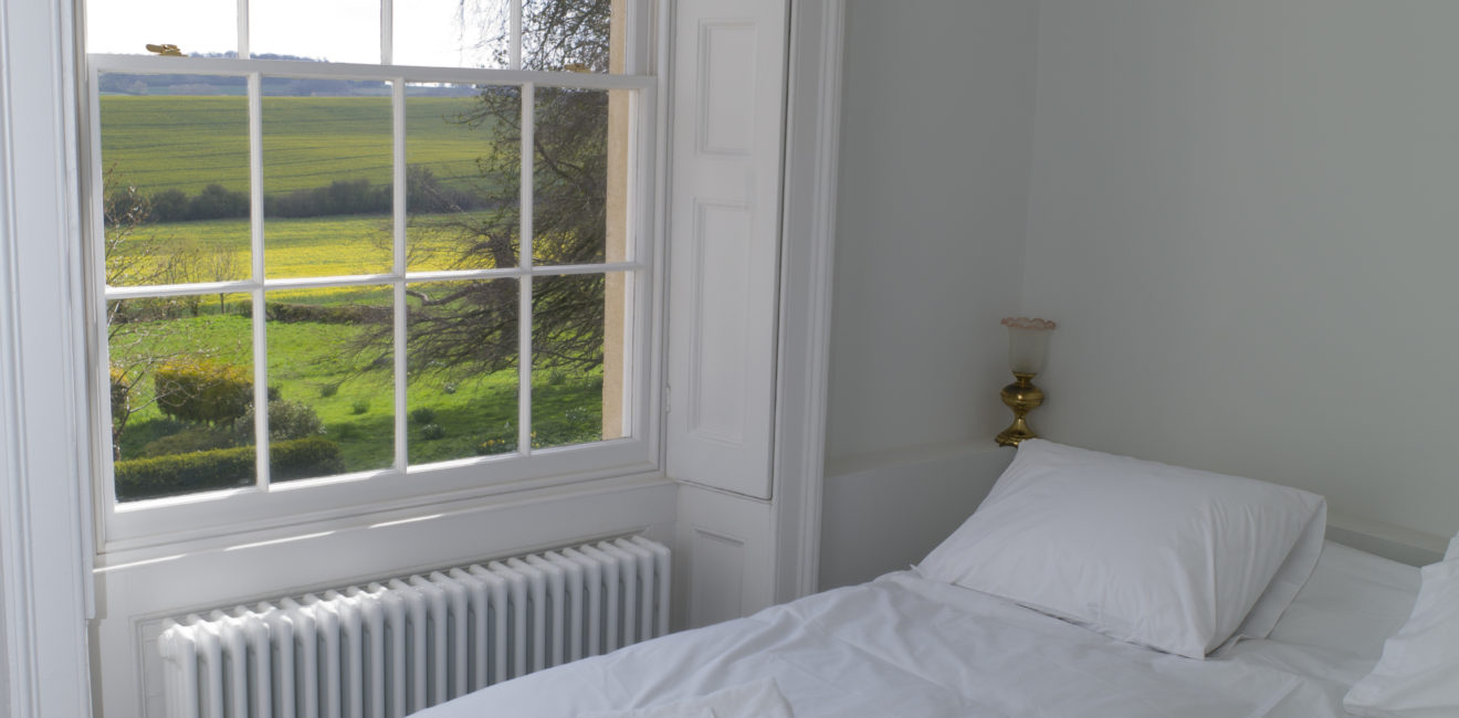 View from one window out to the green South Ormsby Estate parklands from a small bedroom with white bedding on it.