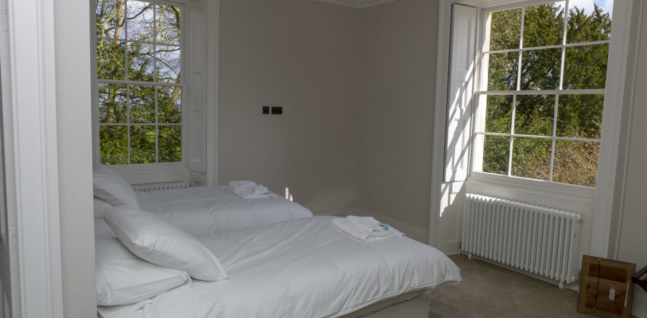 White bedroom at the Rectory at South Ormsby showing view from woodlands out of two large windows.