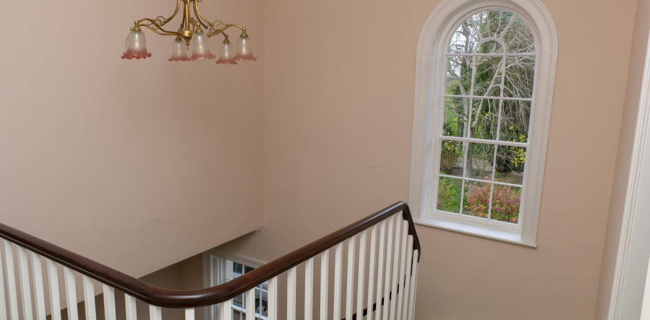 View from top of staircase at the Rectory through a large window set against peach walls.