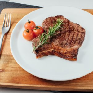 Cooked Lincoln Red Beef steak on white plate with tomato and thyme